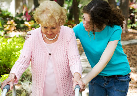 young woman assisting senior woman in walking